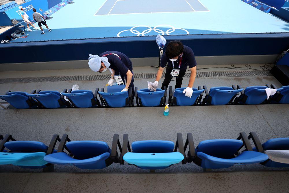东奥尚未开幕,就已传出有多名选手因染疫退赛。图示志愿者正在用抹布给网球场座椅消毒。-路透社-