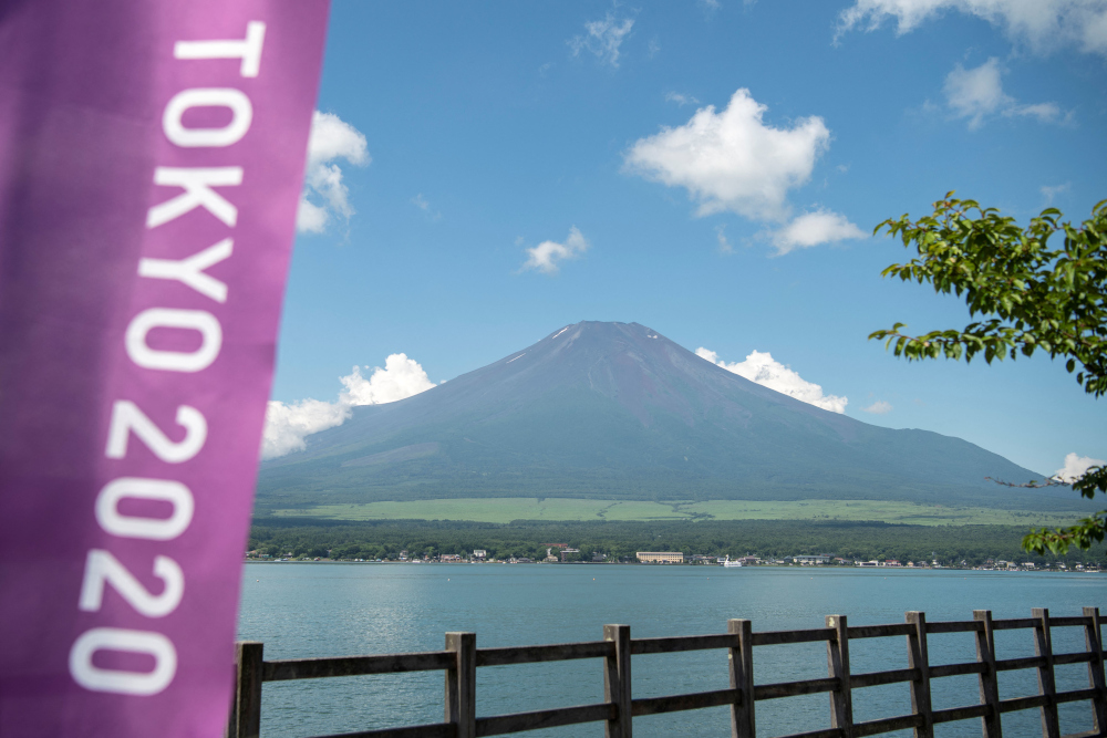 This general view shows Mount Fuji, Japan's highest mountain at 3,776m seen from Lake Yamanaka, next to a Tokyo 2020 Olympics banner July 19, 2021. — AFP pic