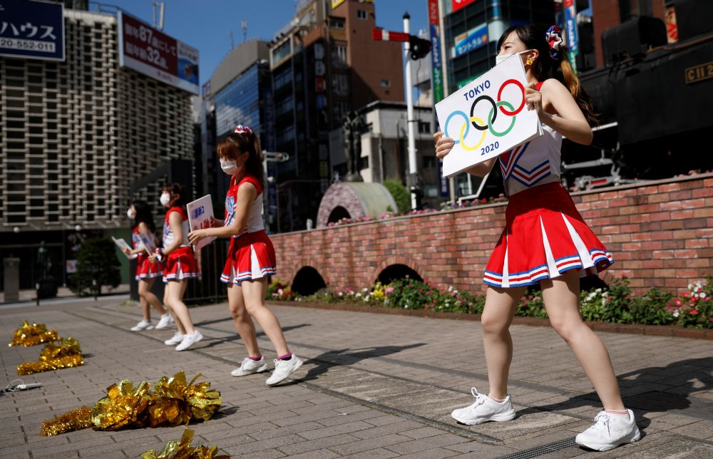 Cheerleaders from the 'All Japan Cheer Organisation' perform in front of the Shimbashi Station in Tokyo July 22, 2021. — Reuters pic