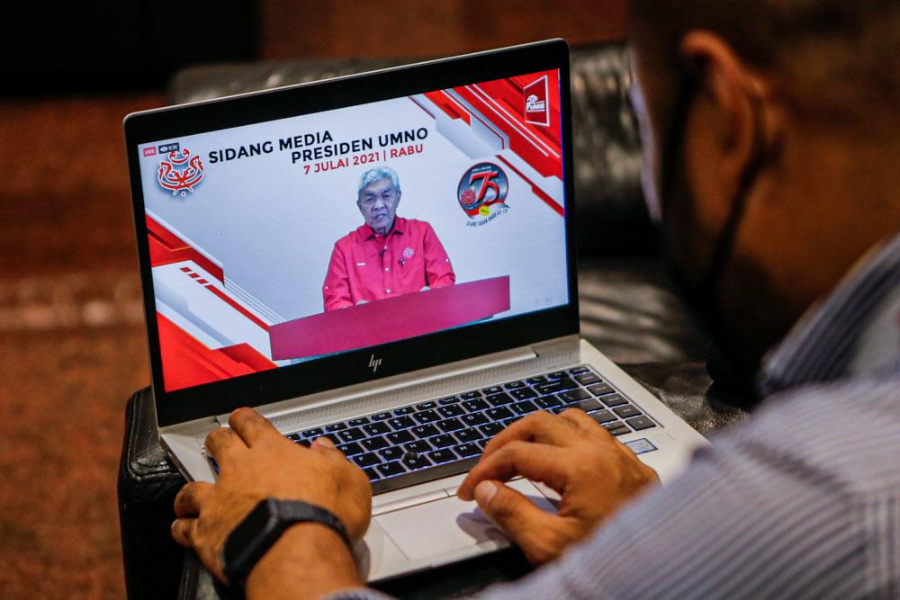 Members of the media watch a livestream of Umno president Datuk Seri Ahmad Zahid Hamidi's online press conference at Umno headquarters in Kuala Lumpur, July 7, 2021. — Picture by Hari Anggara