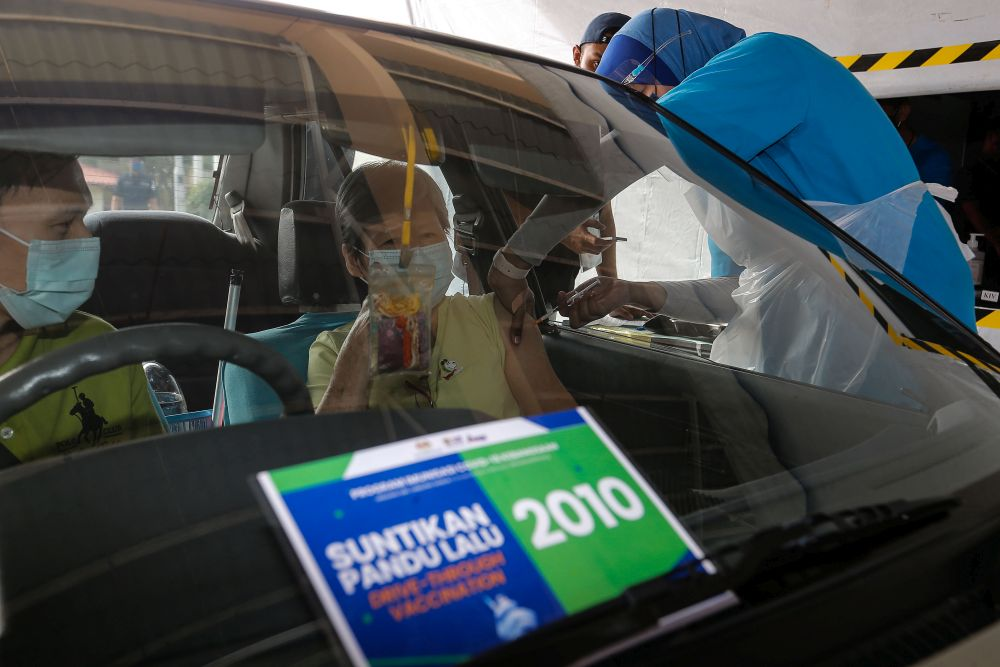 A woman receives her Covid-19 jab at Universiti Sains Malaysia's drive-through vaccination centre in Penang July 23, 2021. — Picture by Sayuti Zainudin