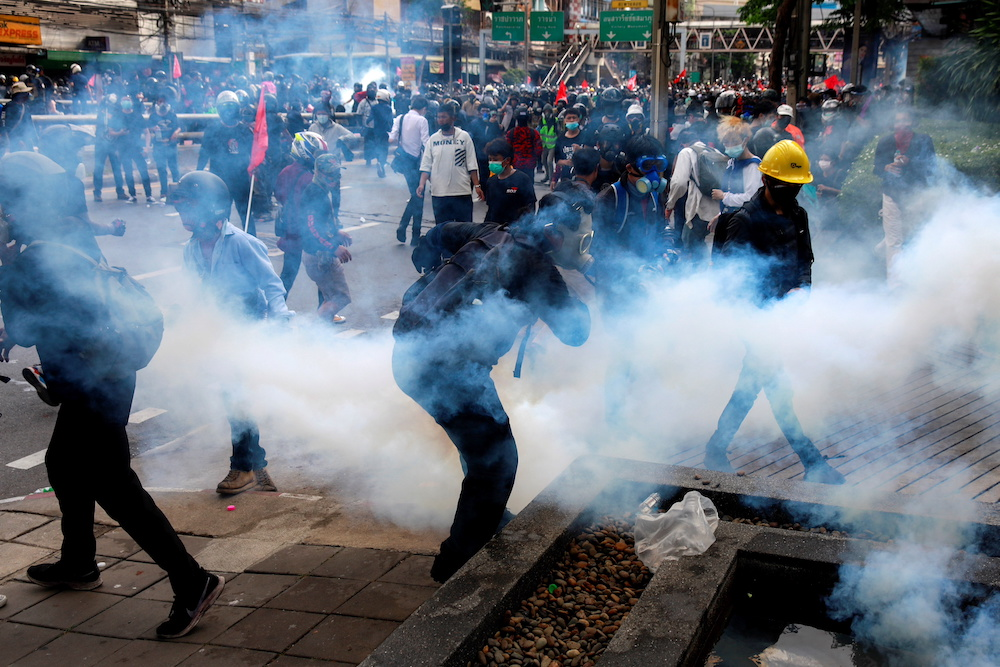 Demonstrators react to tear gas during a clash with police at a protest against what they call the government's failure in handling the Covid-19 outbreak, in Bangkok, Thailand August 7, 2021. — Reuters pic