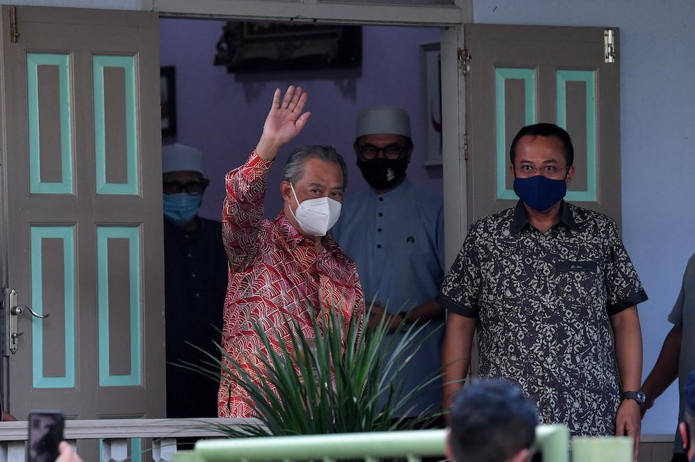 Prime Minister Tan Sri Muhyiddin Yassin waves after his meeting with PAS President Datuk Seri Abdul Hadi Awang at Rusila, in Marang August 12, 2021. — Bernama pic