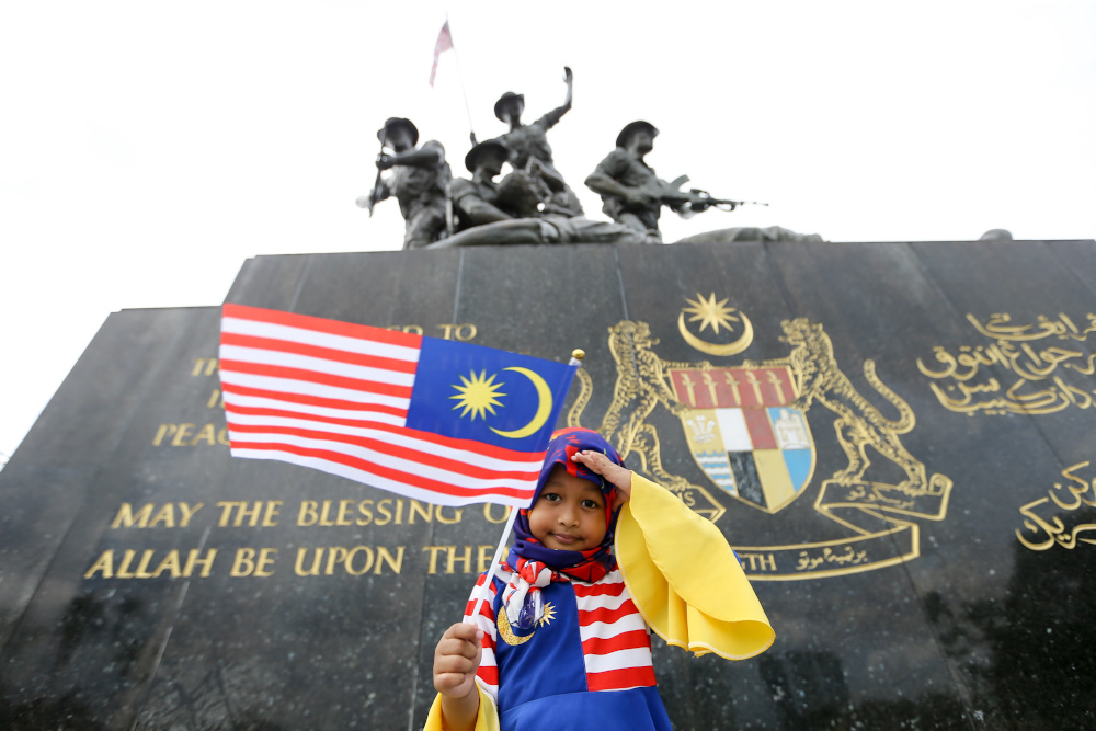 A child poses for a picture while holding a Malaysian flag in conjunction with Merdeka celebrations in Kuala Lumpur August 22, 2021. — Picture by Ahmad Zamzahuri
