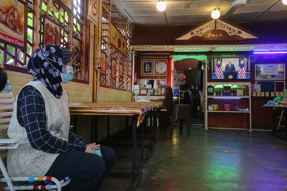 People watch a live telecast of Prime Minister Datuk Seri Ismail Sabri Yaakob's speech at a restaurant in Kuala Lumpur August 22, 2021. — Picture by Yusof Mat Isa