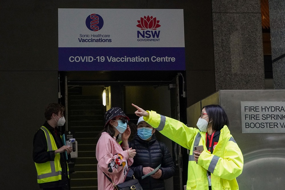 A staff member speaks with people at the entrance to a vaccination centre in Sydney, Australia August 18, 2021. ― Reuters pic