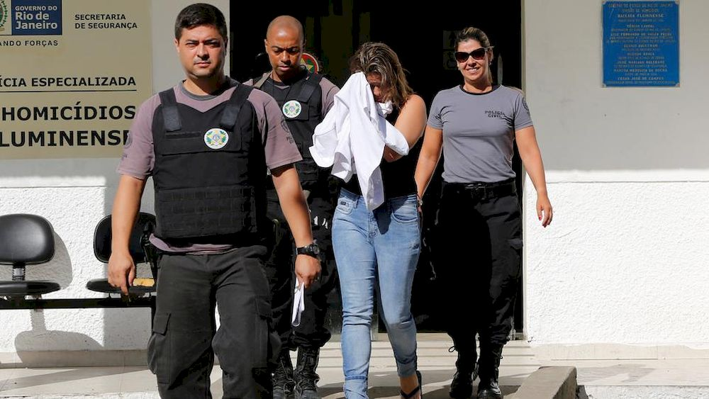 Francoise Souza Oliveira, 40, wife of Greek Ambassador for Brazil Kyriakos Amiridis, is escorted by police officers as she is transferred from the police station to a jail in Belford Roxo, Brazil, December 31, 2016. — Reuters pic