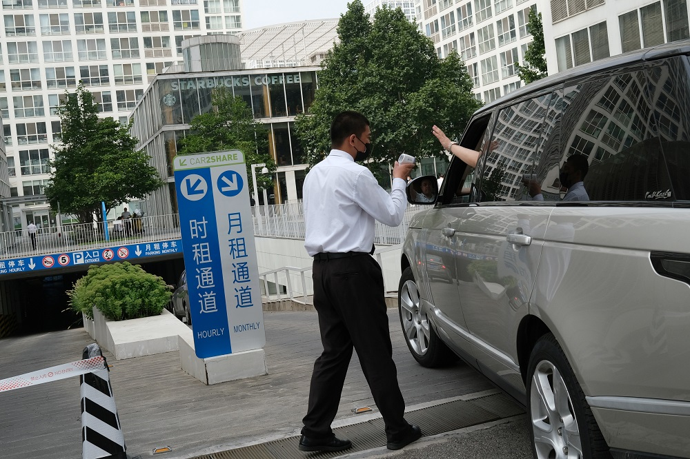 A security guard checks the temperature of a driver at an entrance to a parking lot of an office and commercial compound, following new cases of Covid-19, in Beijing, China August 3, 2021. ― Reuters pic