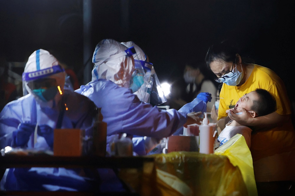 A medical worker in protective suit conducts a swab test following a new case of Covid-19 in Shanghai, China August 2, 2021. Picture taken August 2, 2021. ― cnsphoto via Reuters