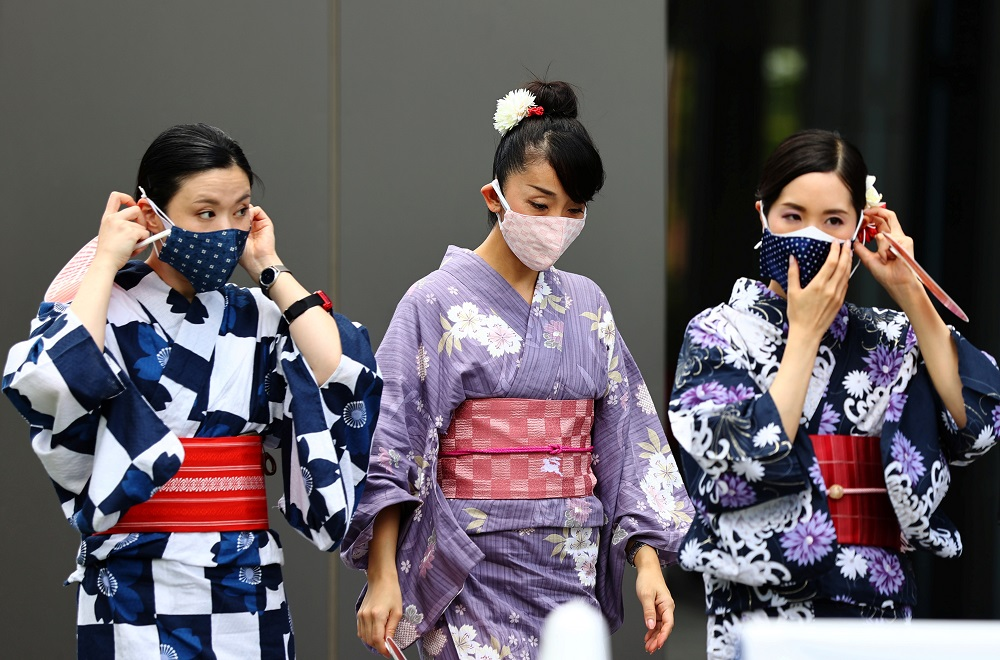Women in traditional costumes, wearing protective face masks, walk outside the National Stadium in Tokyo, Japan August 3, 2021. ― Reuters pic