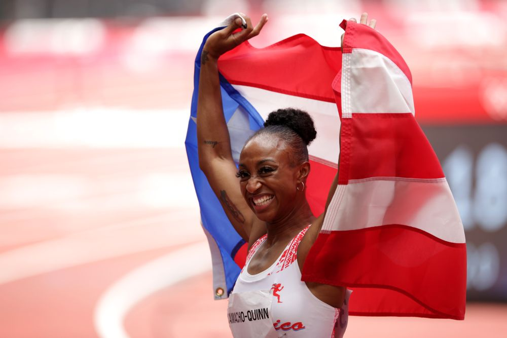 Jasmine Camacho-Quinn of Puerto Rico celebrates with her national flag after winning gold during the women's 100m hurdles final at the Olympic Stadium August 2, 2021. — Reuters pic
