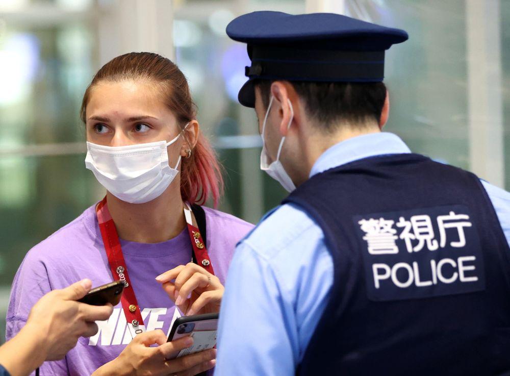 Belarusian sprinter Krystsina Tsimanouskaya talks with police officers at Haneda international airport in Tokyo August 1, 2021. — Reuters pic