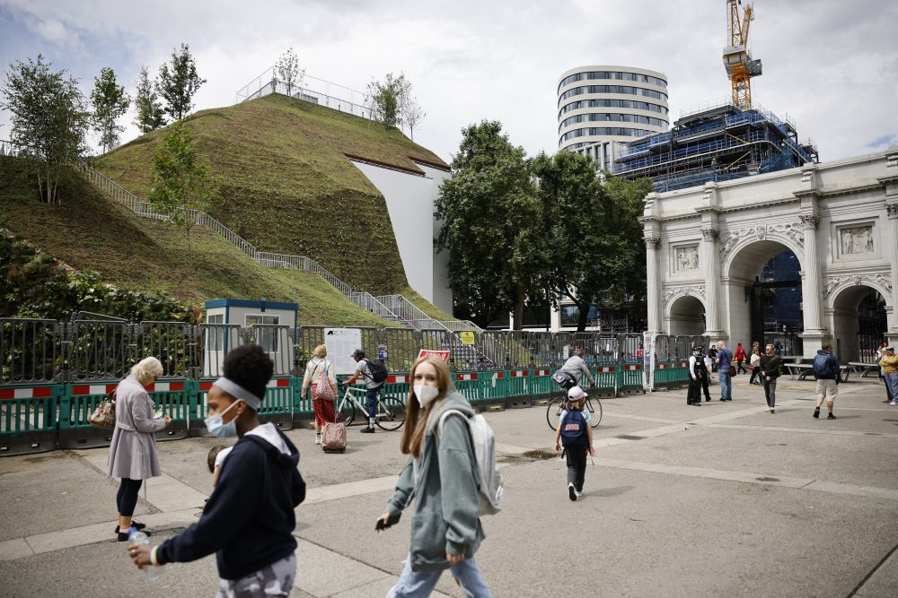 Pedestrians walk past the Marble Arch Mound, a new temporary attraction, next to Marble Arch in central London. — AFP pic