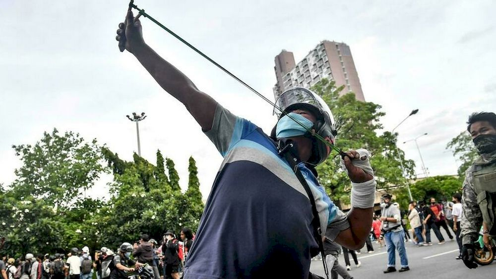 A protester uses a slingshot against police at the rally in Bangkok. — AFP pic