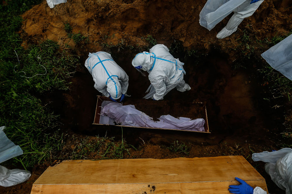 Health personnel bury the body of a Covid-19 victim for burial at Bagan Ajam Muslim Cemetery, August 24, 2021. — Picture by Sayuti Zainudin