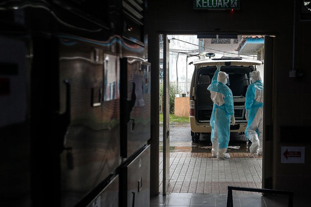 2021 年 8 月 24 日,法医小组准备将一名最近去世的 Covid-19 患者的尸体从槟城综合医院运送到墓地。 — 图片来自 Sayuti Zainudin