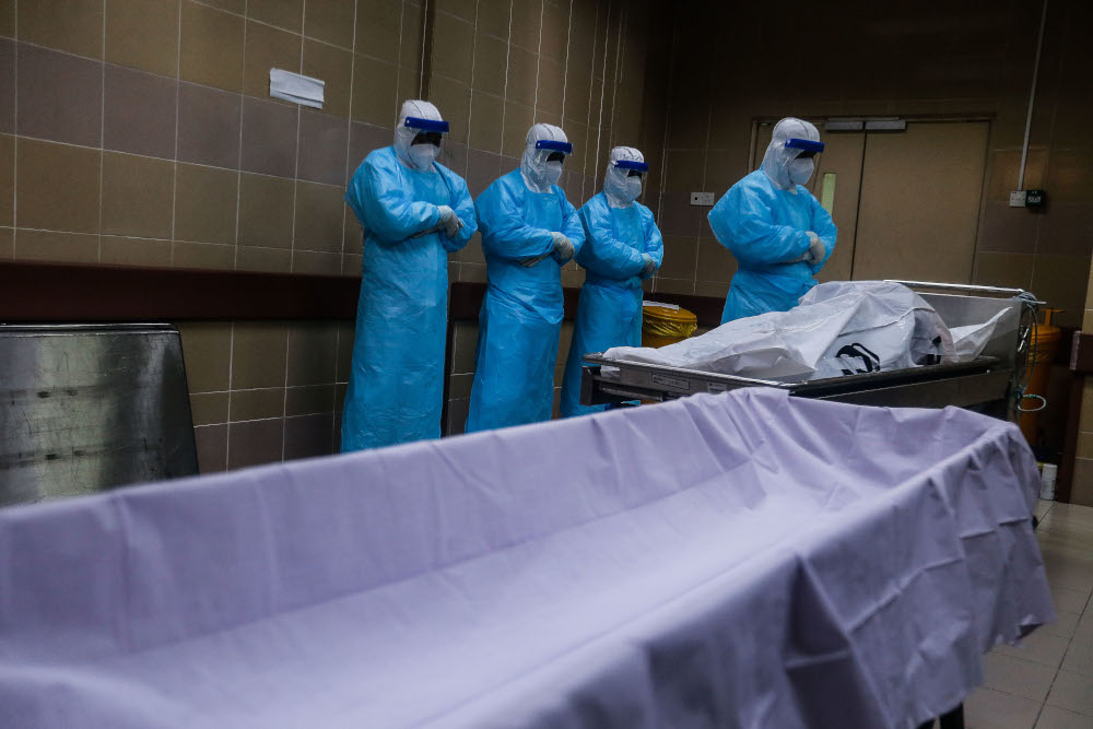 Forensic personnel conduct prayers for a recently deceased Covid-19 patient as they prepare the body for burial at the Penang General Hospital, August 24, 2021. — Picture by Sayuti Zainudin