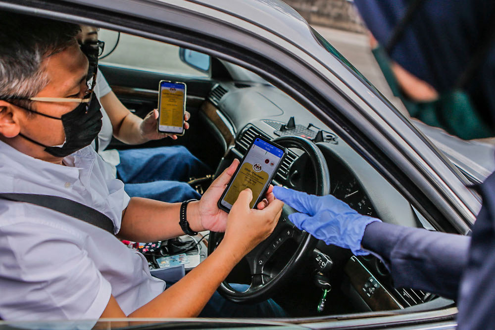 A man and his passenger show the Covid-19 digital vaccination certificate to police at the Plaza Bentong roadblock, August 11, 2021. ― Picture by Hari Anggara