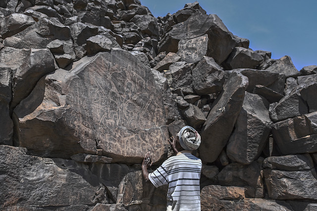 Ibrahim Dabale, 50, a native and art guardian, shows art etched into volcanic rock at the remote Abourma Rock Art site in the Makarassou Massif of Tadjoura Region, nothern Djibouti. — AFP pic
