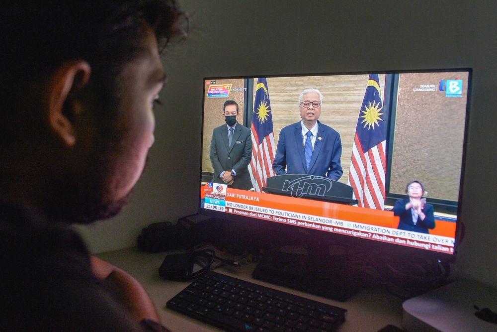 A man watches a live telecast of Prime Minister Datuk Seri Ismail Sabri Yaakob's speech in Kuala Lumpur August 27, 2021. — Picture by Miera Zulyana