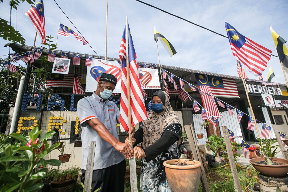 Jamaludin and wife Masitah Ismail placing one of the flags in the decor. — Picture by Farhan Najib
