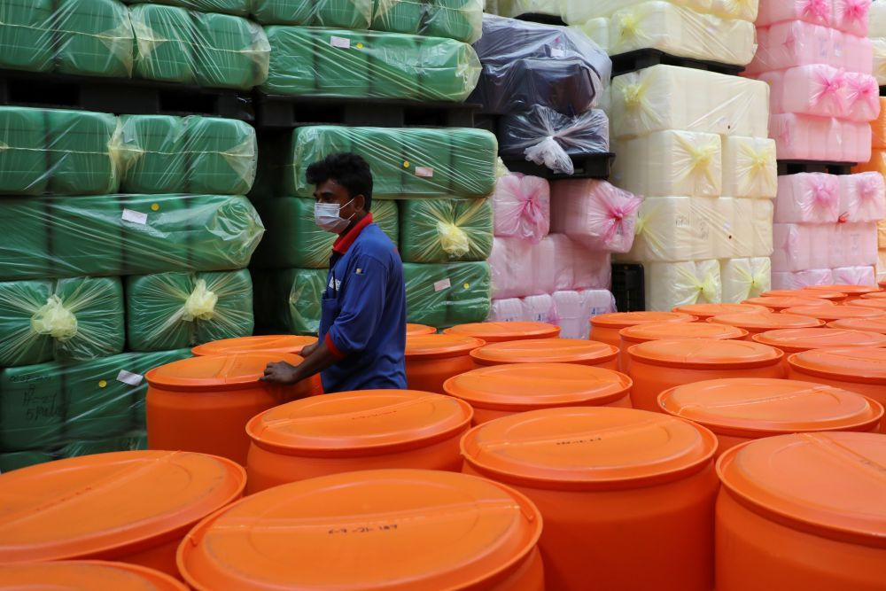 A foreign worker works at a plastic containers factory during an enhanced lockdown, amid the coronavirus disease outbreak, in Klang July 8, 2021. — Reuters pic