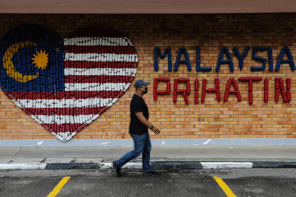 A man waks past a Malaysia Prihatin wall decoration in Kuala Lumpur August 25, 2021. — Picture by Ahmad Zamzahuri