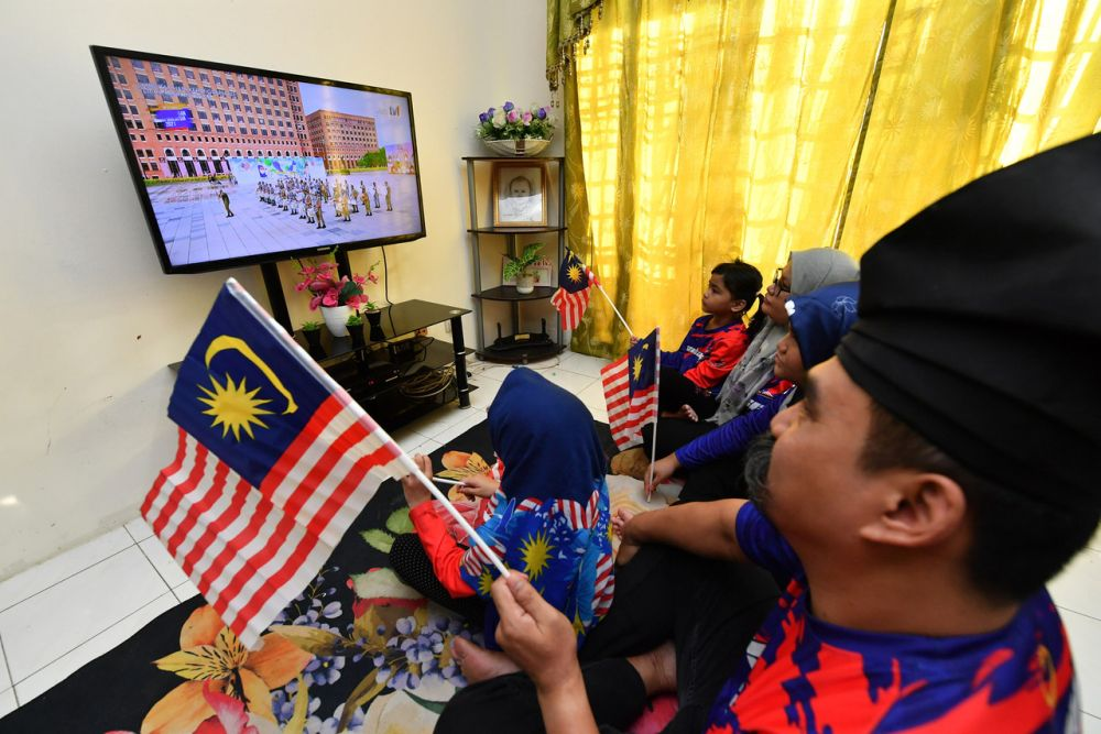 A man and his family watch a live broadcast of the National Day celebrations in Putrajaya August 31, 2021. — Bernama pic
