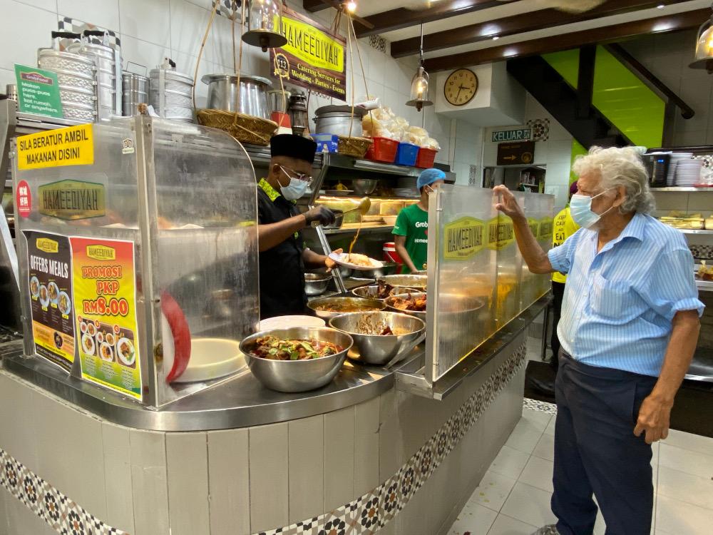 Hameediyah Restaurant director Mohd Riyaaz (left) packing up nasi kandar for a customer to take away. ― Picture by Steven Ooi KE