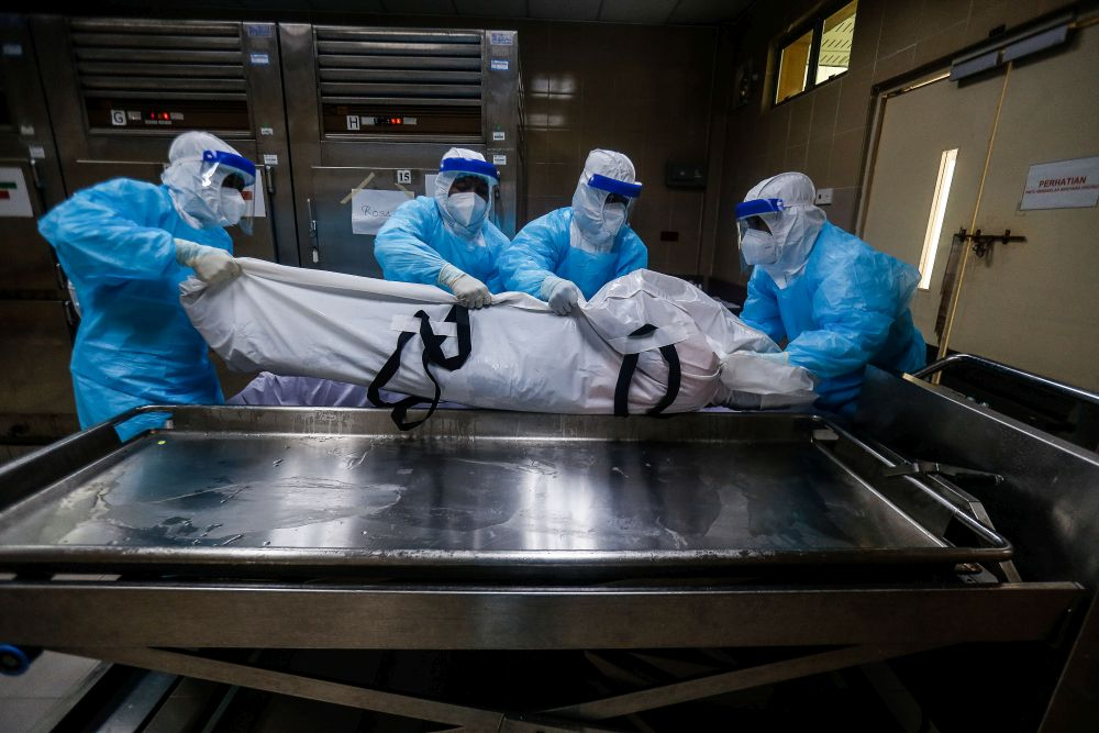 Forensics personnel transfer the body of a recently deceased Covid-19 patient out of the morgue at the Penang General Hospital, August 24, 2021. — Picture by Sayuti Zainudin