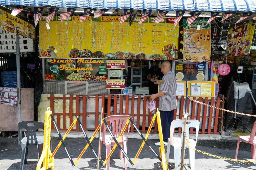 A customer packs food to go at Sinar Malam Cafe in Taman Tun Sardon, Penang, August 11, 2021. ― Picture by Sayuti Zainudin