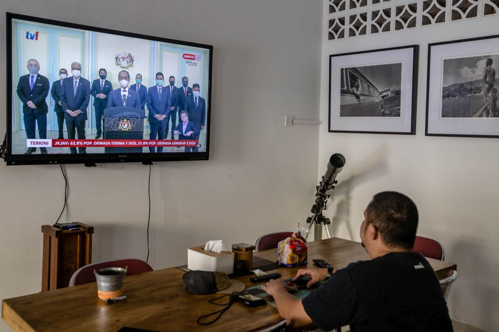A man watches a live telecast of Prime Minister Tan Sri Muhyiddin Yassin's speech in Kuala Lumpur August 4, 2021. — Picture by Firdaus Latif