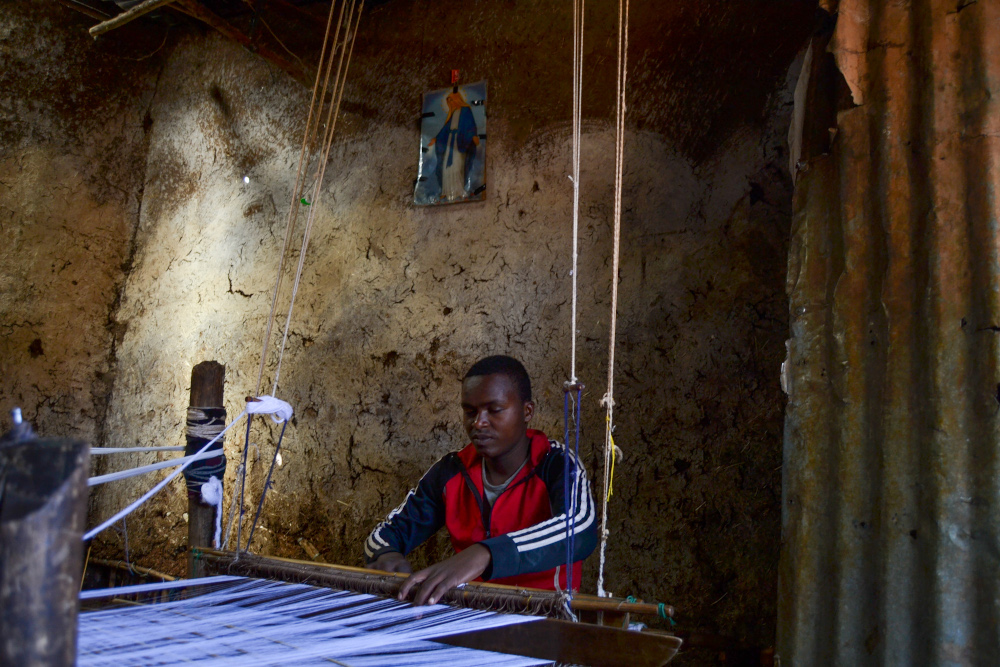 A teenage boy handweaves a traditional Ethiopian scarf in Addis Ababa March 2021. — Thomson Reuters Foundation pic
