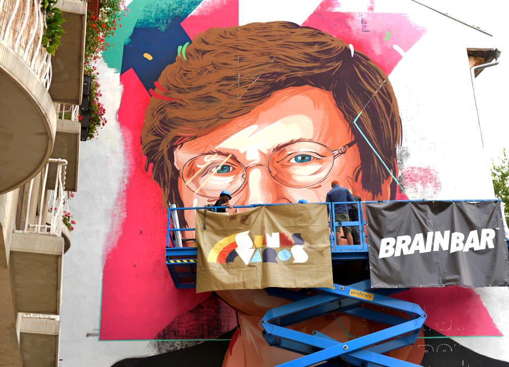 A painter makes finishing touches on a mural showing a portrait of Katalin Kariko, a Hungarian-born scientist and senior vice president at BioNTech, who laid the groundwork for the mRNA vaccines fighting Covid-19 in Budapest August 28, 2021. — Reuters pic