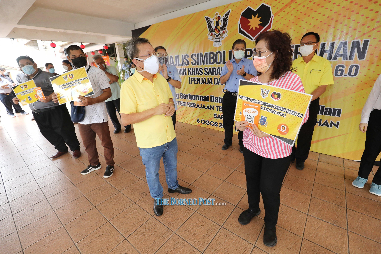 Dr Sim (second right) greets a representative during the symbolic handover ceremony. — Picture by Chimon Upon/Borneo Post