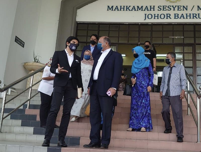 Muar MP Syed Saddiq Syed Abdul Rahman (left) has a word with his lawyer Gobind Singh Deo at the Johor Baru Sessions Court August 5, 2021. — Picture by Ben Tan