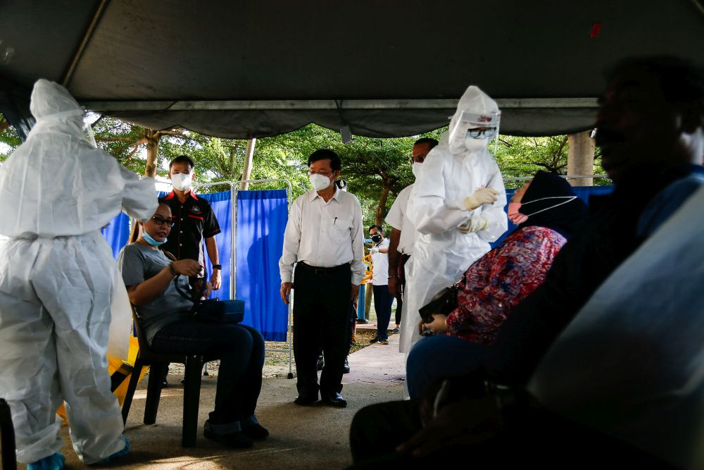 Penang Chief Minister Chow Kon Yeow (centre) is pictured during a visit to the mass screening exercise in Taman Manggis, George Town August 12, 2021. — Picture by Sayuti Zainudin