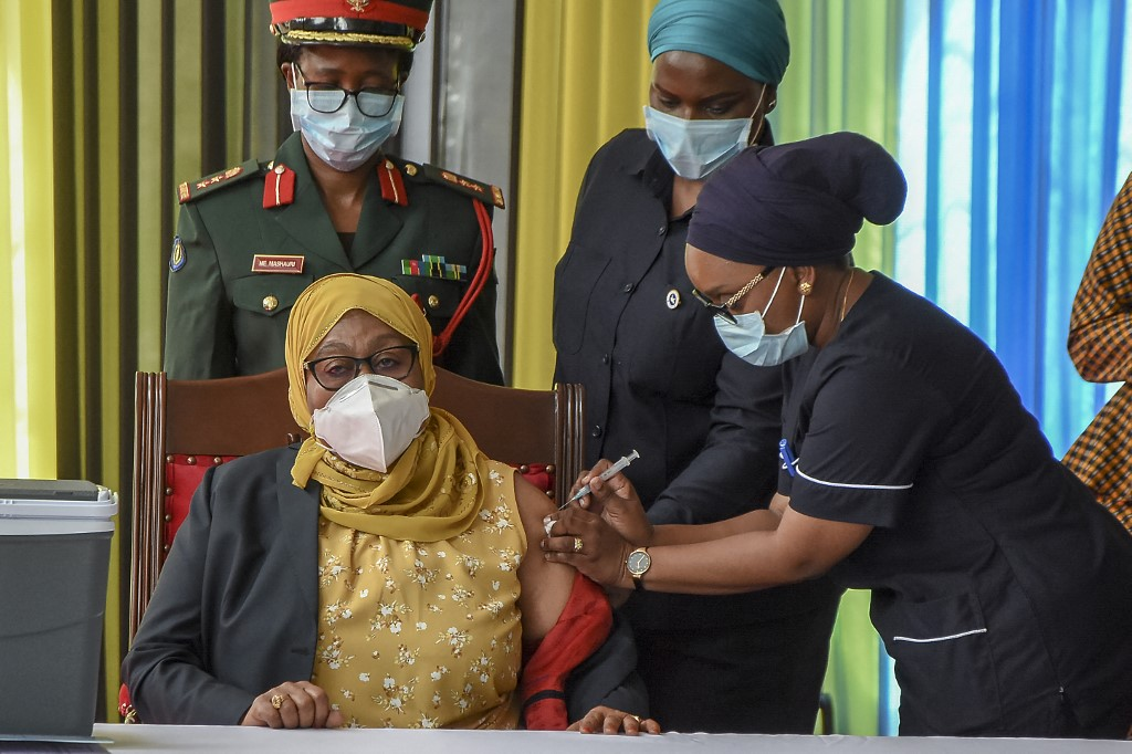 Tanzania's President Samia Suluhu Hassan (left) receiving a shot of the Johnson & Johnson vaccine from a health worker at the State House in Dar es Salaam, on July 28, 2021. — AFP pic