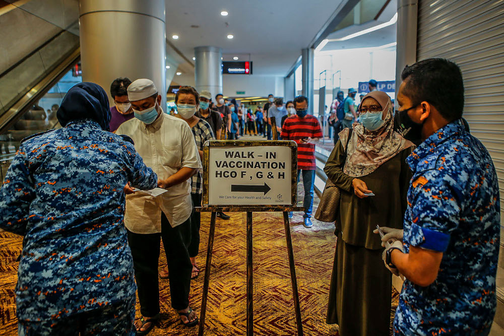 Walk-in vaccine recipients queue up for registration for their Covid-19 jabs at the Kuala Lumpur Convention Centre vaccination centre, August 2, 2021. ― Picture by Hari Anggara