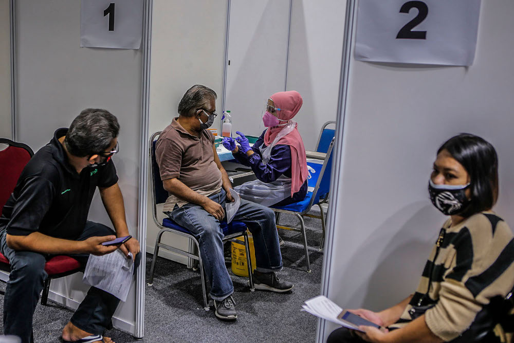 Walk-in recipients receive their Covid-19 jabs at the Kuala Lumpur Convention Centre vaccination centre, August 2, 2021. ― Picture by Hari Anggara
