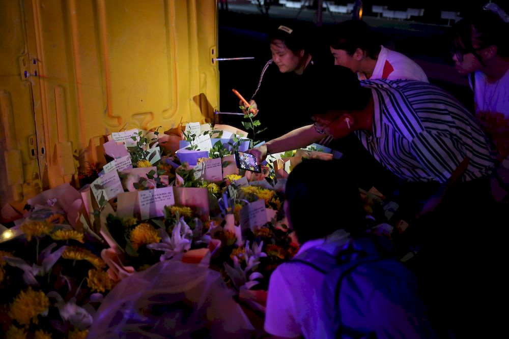 People hold their mobile phones in front of flowers placed near an entrance to a subway station of Metro Line 5 in memory of flood victims following heavy rainfall in Zhengzhou, Henan province, China July 26, 2021. — China Daily pic via Reuters