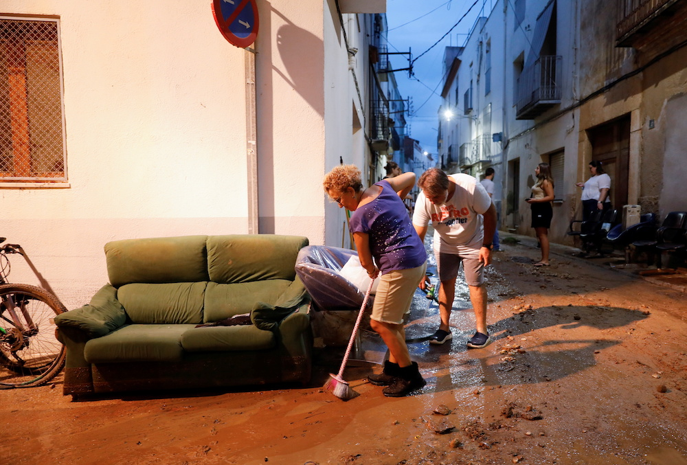 People clean the mud of a street after floods caused by heavy rains in Alcanar, Spain September 1, 2021. — Reuters pic