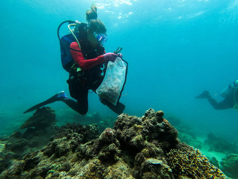 Diving instructor Carmela Sevilla holds a mesh bag filled with trash during an underwater cleanup drive in Bauan, Batangas Province, Philippines September 18, 2021. — Reuters pic