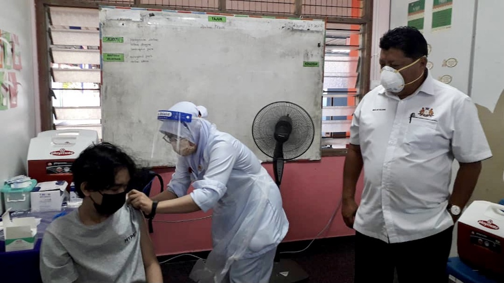 Johor Education, Information, Heritage and Culture Committee chairman Mazlan Bujang (far right) observes the vaccination of a student during his visit to Sekolah Menengah Kebangsaan (SMK) Taman Daya in Johor Baru September 20, 2021 — Picture by Ben Tan