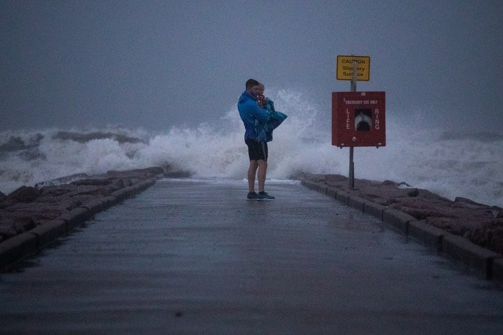 Local resident John Smith holds his 18-month-old son Owen as he stands near breaking waves on a pier ahead of the arrival of Tropical Storm Nicholas in Galveston, Texas September 13, 2021. — Reuters pic