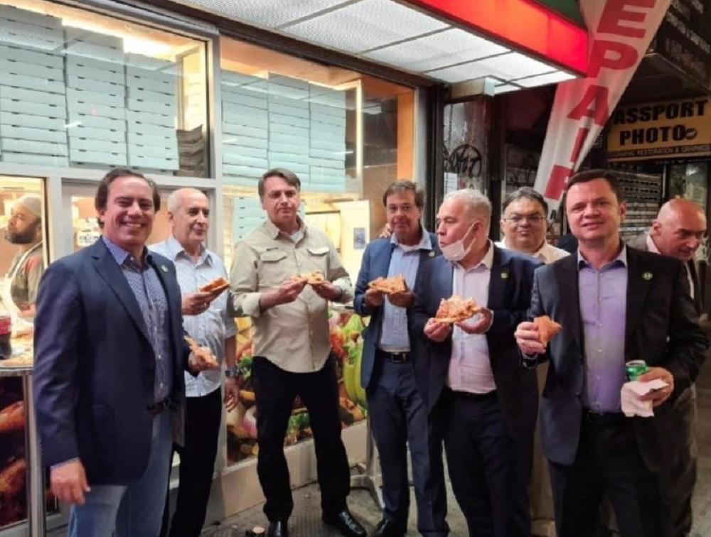 """巴西总统府秘书长拉莫斯在推特上传博索纳罗(左3)在路边与其他访团官员一起吃披萨的照片,文字注明:""""纽约的豪华晚宴。""""-路透社-"""