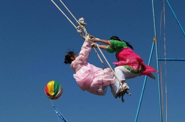 韩国女孩子会在秋夕节当天,穿上艳丽的传统服饰玩跳板、秋千等游戏,男孩子则拔河、摔跤等-图取自网络-