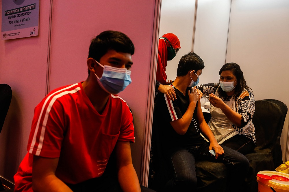 Twins Danial Husni (left) and Danish Husni, 16, receive their Covid-19 vaccination at the Subterranean Penang International Convention and Exhibition centre in Bayan Baru September 22, 2021. — Picture by Sayuti Zainudin