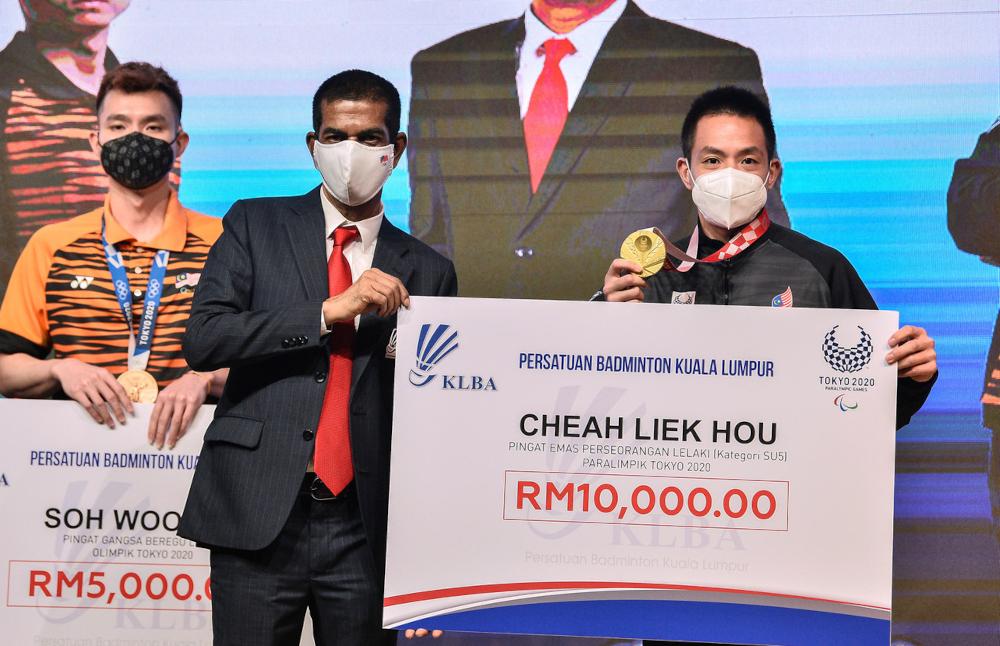 KLBA president Datuk Seri Jahaberdeen Mohamed Yunoos hands a mock cheque to national para badminton champion Cheah Liek Hou at Academy Badminton Malaysia in Bukit Kiara, September 20, 2021. — Bernama pic