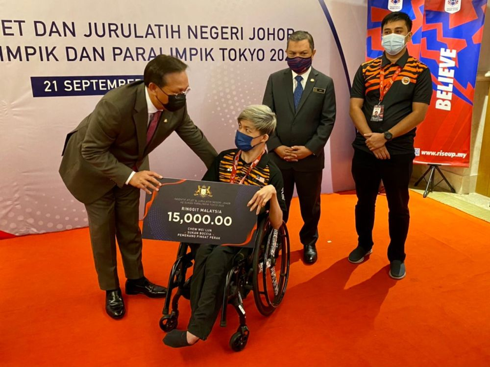 Johor Mentri Besar Datuk Hasni Mohammad (left) presents a mock cheque to Tokyo 2020 Paralympic Games silver medallist Chew Wei Lun September 21, 2021. — Picture by Ben Tan